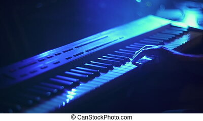 Music recording studio. Musician producing song in studio. Hands playing on piano electronic keyboard. Sliding video, blue light, shallow depth of field