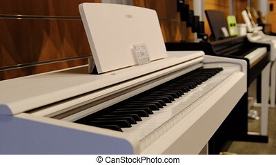 Music shop. Many electric grand pianos and synthesizers are sold in a shop window. A row of musical instruments is sold in the Store. Keyboard musical instruments displayed in the workshop. 4K
