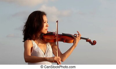 Music - Violinist playing on violin while sunset