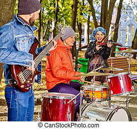 Music street performers with girl violinist having blue hair...