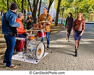 Music street performers with girl violinist on autumn outdoor.