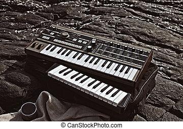 Music synthesizer lying on rocks close up