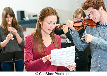 music teacher tutoring young man to play violin