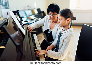 music teacher with the pupil at  lesson piano