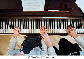 music teacher with the pupil at   lesson piano,