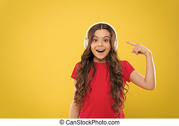 Music to your ears. Adorable child listen to music playing in earphones on yellow background. Little girl enjoying her favorite music. Cute small kid listening to music in headset, copy space