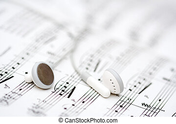 Music - White earbuds on book of musical notes