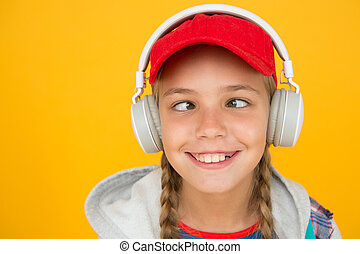 Music with emotions. Squint-eyed kid on yellow background. Funny child listen to music in stereo headphones. Small child enjoy music playing in earphones. Non-stop music for more fun