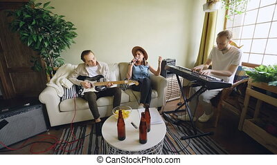 Musical band is rehearsing at home, woman is singing and men...