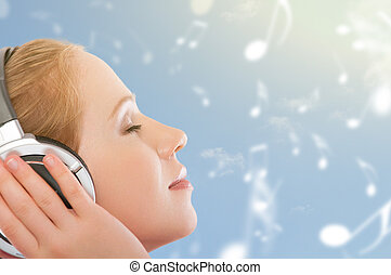 musical concept. woman with headphones relax, enjoy the music on the sky background with notes
