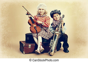 musical duo - Cute little boy with his old saxophone is...