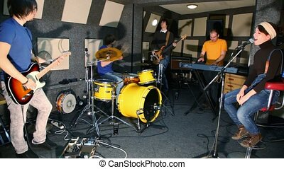 musical group of five persons playing in recording studio