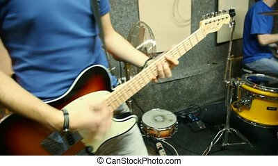 musical group of five persons playing in studio, moving camera