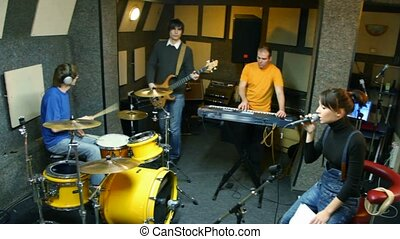 musical group playing in studio, moving camera