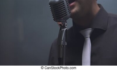 View on rock musician sings in studio, close-up