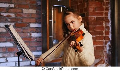 Musical lesson. A little girl playing viollin by notes....