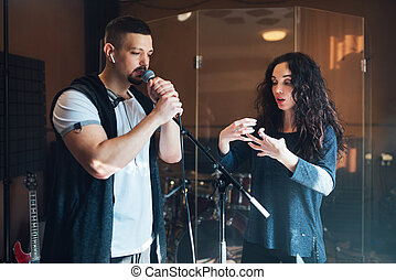 Musical teacher coaching a young male vocalist
