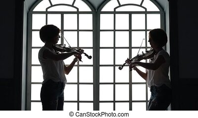 Musican plays the violin in the evening against the background of a window. Silhouette