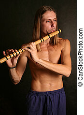 A man playing his wind instrument with expression