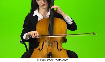 Musician bows the strings of the viololla playing . Green...