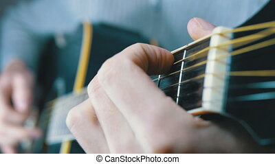 Musician Clamps the Chords on the Acoustic Guitar Frets....