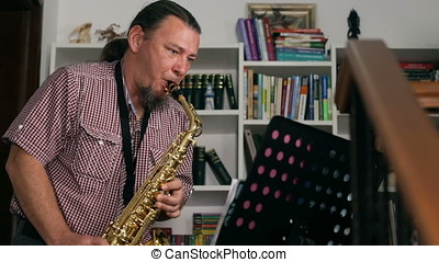 Musician composing jazz saxophone music, bookshelves on...