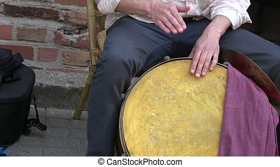 Musician drummer hands playing with big drum