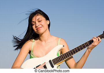 Girl in green dress playing a guitar