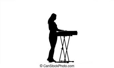 Musician girl in silhouette playing the electronic piano. Slow motion