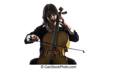 Musician girl plays a violoncello rehearsing a composition....