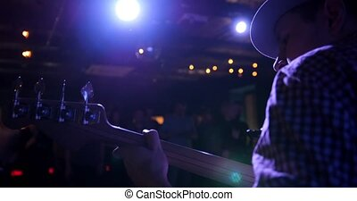 Musician - guitarist in hat plays guitar in night club, rear view