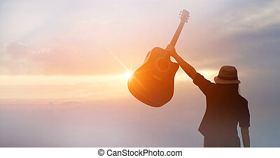 Musician holding acoustic guitar in hand of silhouette on sunset background