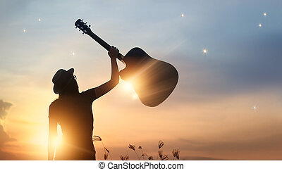 Musician holding guitar in hand of silhouette on sunset nature background