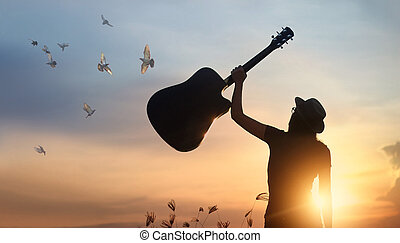 Musician holding guitar in hand with free bird of silhouette on sunset nature background