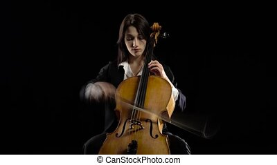 Musician in a dark room sits and plays a violoncello...