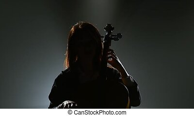 Musician in a dark room sits on a chair and plays the violoncello. Silhouette. Black smoke background
