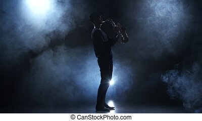Musician in a smoky studio. Slow motive on the saxophone