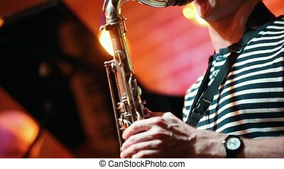 Musician in a striped t-shirt playing the saxophone at a...