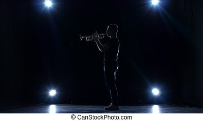 Musician in dark studio with spotlights playing trumpet slow...