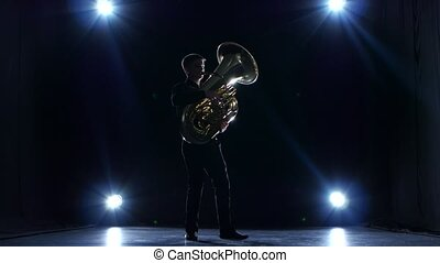 Musician in dark studio with spotlights playing tuba slow...