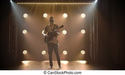 Musician in ethnic African costume plays the guitar in a dark studio. Black barefoot man closed his eyes and enjoys playing an instrument in the background of lights. Slow motion.