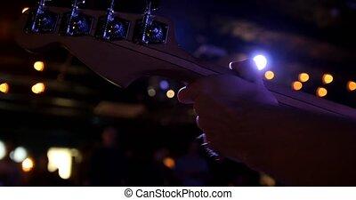 Musician in night club - guitarist holds the guitar soundboard