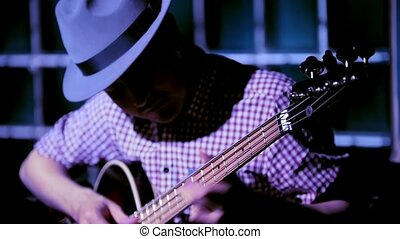 Musician in night club guitarist plays bass guitar, close up