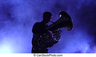 Musician in smoky studio playing in tuba, silhouette. Slow motion