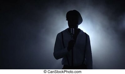 Musician in the smoke at the white light singing at the microphone. Black background. Silhouette. Slow motion