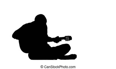 Musician is playing guitar sitting on the floor. Silhouette. White background