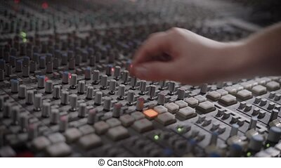 Musician is working in a recording studio with a mixing...