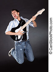 Musician jumping with his guitar