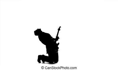 Musician kneeling playing the electric guitar. Silhouette. Slow motion