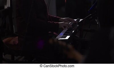 Musician man play keyboard on dark stage - Musician man play...